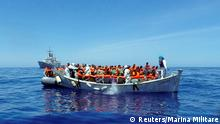 Migrants sit in their small boat as an Italian navy ship approaches to rescue them.