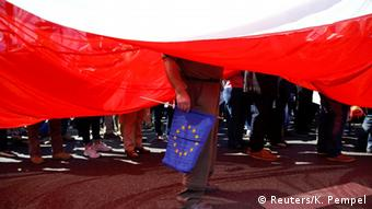 A giant Polish flag provides a backdrop for demonstrators