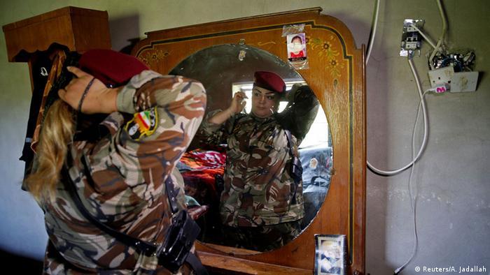 Die kurdische Kämpferin Haseba Nauzad bindet sich die Harre (Foto: REUTERS/Ahmed Jadallah)
