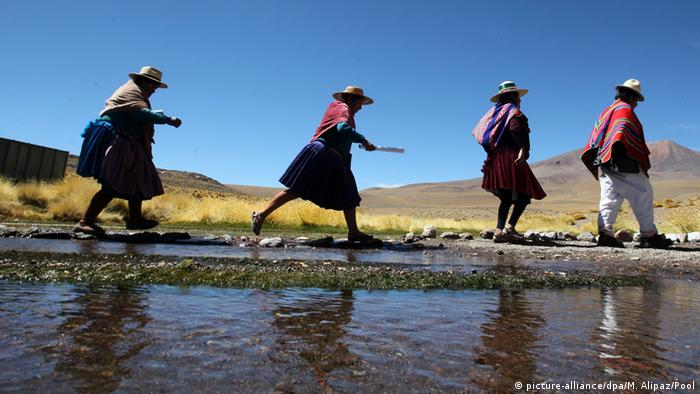 Four women walking along a river bank