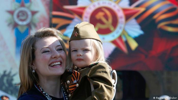 Счастливая женщина держит на руках ребенка в советской военной форме
