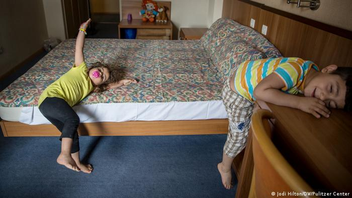 Two children lay on a bed