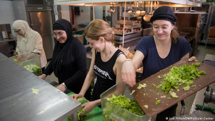 Italian volunteers and Syrian refugees work together in the hotel's kitchen to cook lunch