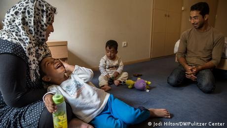 Ali Jaffari and his family sit on the floor in a hotel room