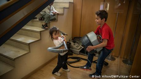 A boy and girl wrestle with a vacuum cleaner