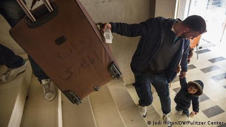 A man holds one end of a suitcase as he helps a small boy to climb stairs