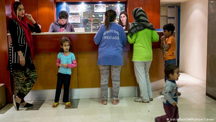 Adults and children stand at the reception desk at City Plaza