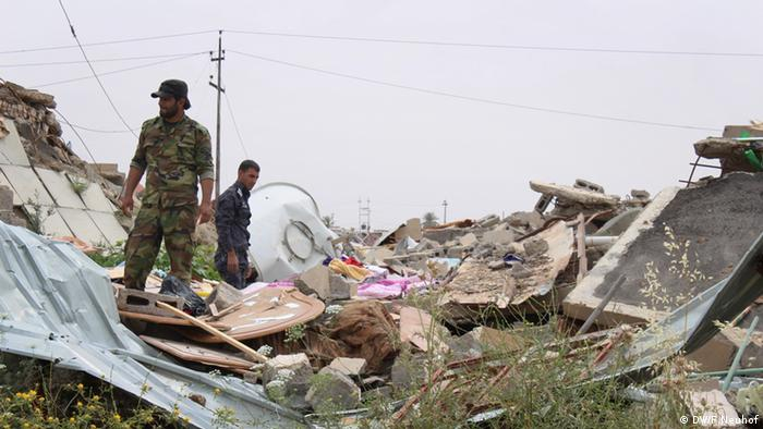 A local Turkmen fighter sifts through the rubble of his family's house