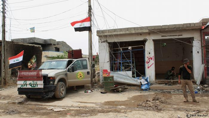 A man stands in front of a ruining building next to a truck belonging to a Shiite militia