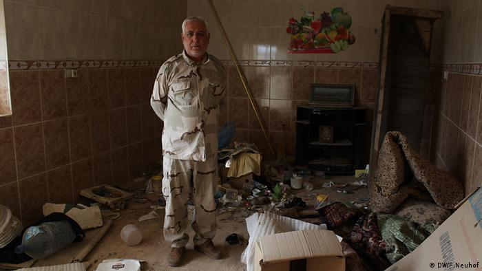 Adel Akbar stands in a room of his house that has been left in disarray