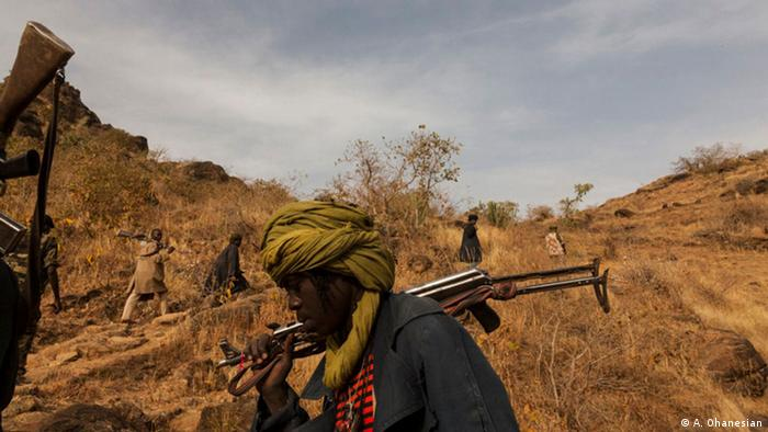 Man holding rifle, Copyright: Adriane Ohanesian