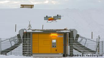 A DHL 'parcelcopter' hovers above a 'packstation'