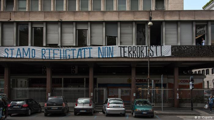 A sign on an occupied office building in central Rome reads, 'We are refugees, not terrorists'