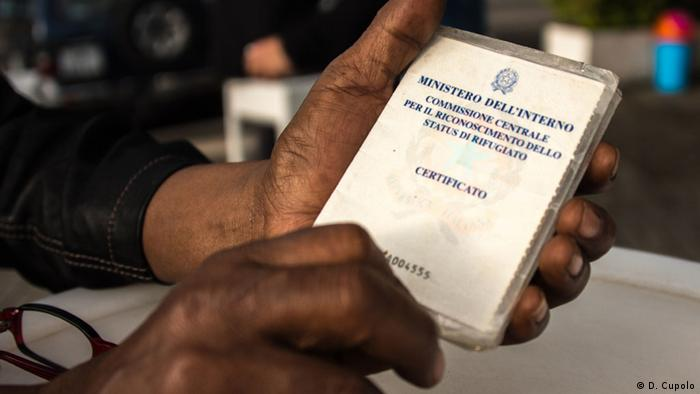 Moulgeta Gaffi, an Ethiopian living in Rome for 14 years, holds his refugee identification card