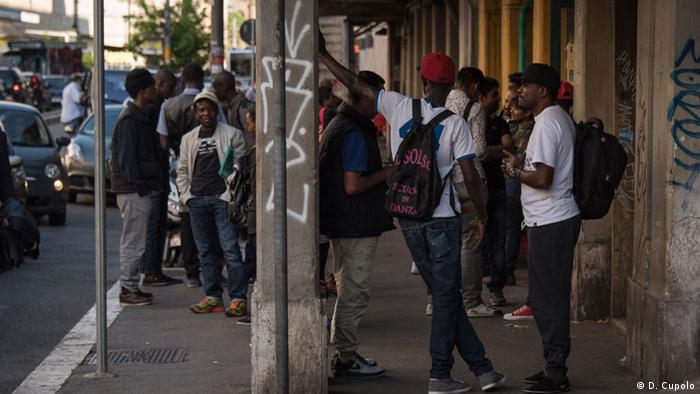 Asylum-seekers hang out across the street from the main train terminal in Rome, a common gathering place for new arrivals
