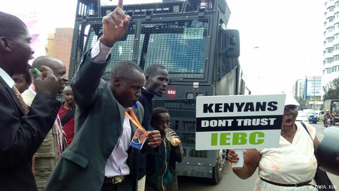 Oppositions members demonstrate in Nairobi holding up a card saying Kenyans don't trust the IEBC