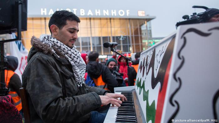 Aeham Ahmad playing on a square by Cologne's Central Station (picture-alliance/dpa/M. Hitij)