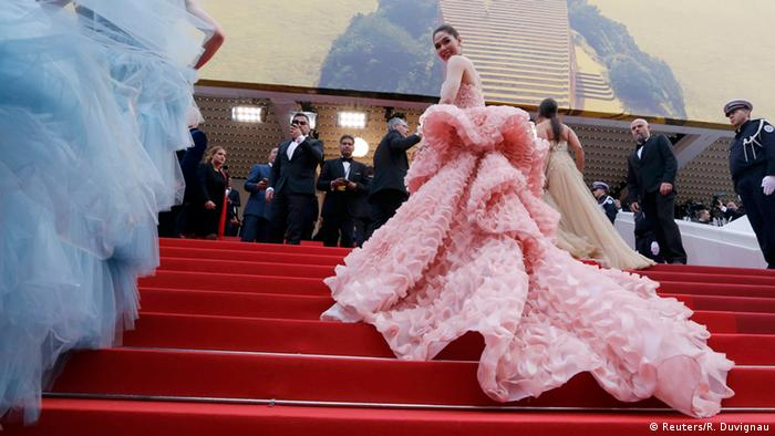 Woman in an outrageously long pink dress climbs a red carpet staircase