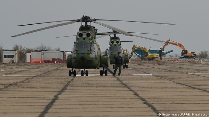 Diggers and Romanian military helicopters stand on the runway prior to the official groundbreaking ceremony at the former Deveselu military airbase in Deveselu village, southern Romania, on October 28, 2013 © Getty Images/AFP/D. Mihailescu