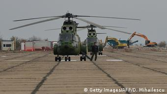 Diggers and Romanian military helicopters stand on the runway prior to the official groundbreaking ceremony at the former Deveselu military airbase in Deveselu village, southern Romania, on October 28, 2013 (Photo: Getty Images/AFP/D. Mihailescu)