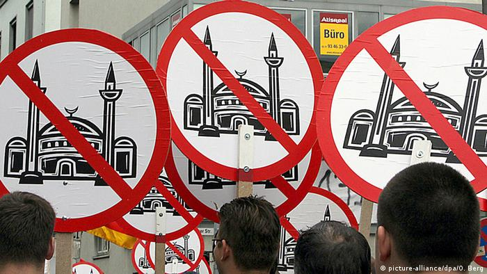 A group of protesters hold up anti-mosque signs. The circular shape resembles traffic signs that prohibit oncoming traffic. A mosque is a printed in the middle of each with a red slash drawn through it