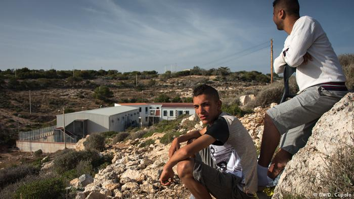 Two young asylum-seekers sit on a bluff on Lampedusa