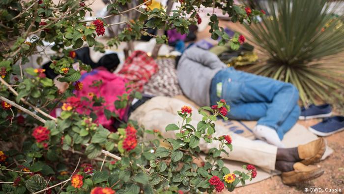Men lie on mats on the ground