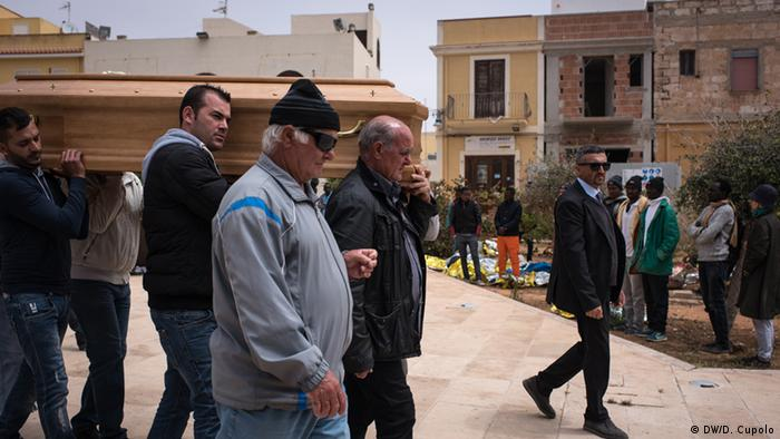 Locals accompany a coffin across a Lampedusa square