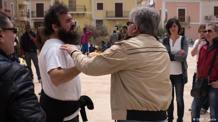 Giacomo Matina (right) argues with a local activist on a plaza in Lampedusa