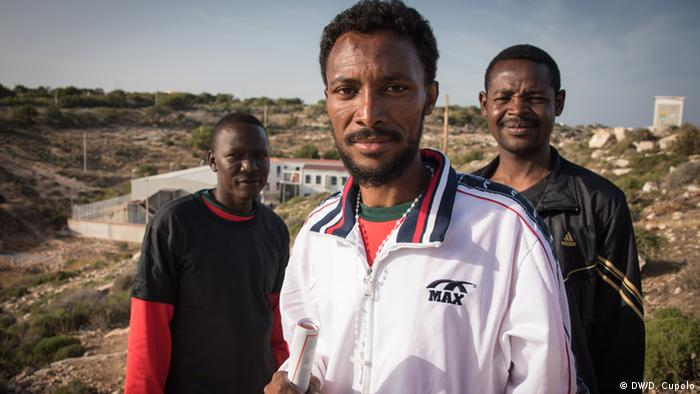 Three asylum-seekers pose for the camera