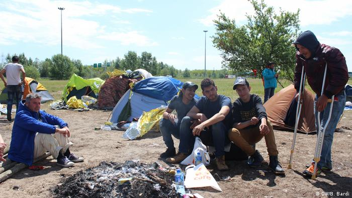 Young asylum-seekers sit in front of a burnt-out campfire outside the transit zone