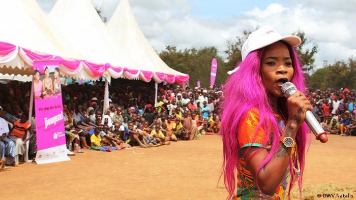 A brightly dressed African women with pink hair speaks at the start of an AIDS test campaign (DW/V.Natalis)
