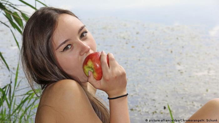 Nackte junge Frau beißt genüsslich in Apfel