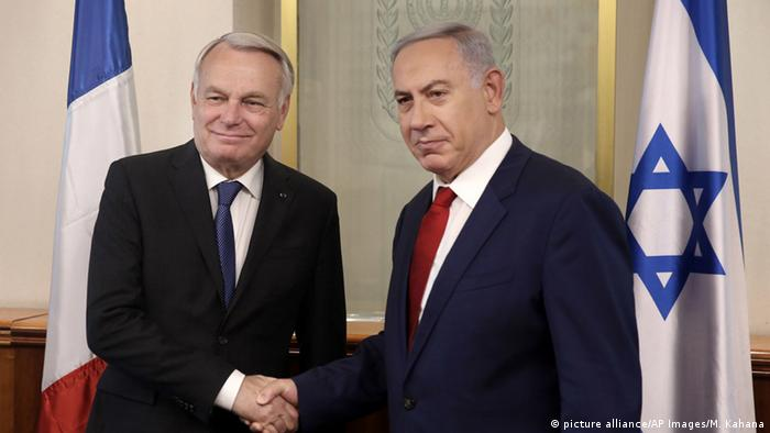 Israeli Prime Minister Benjamin Netanyahu, right, shakes hands with French Foreign Minister Jean-Marc Ayrault