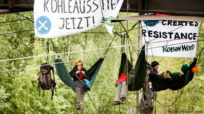 Menschen sitzen in Hängematten in luftiger Höhe mit Plakaten, die den Kohleausstieg fordern