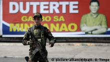 16.5.2016 *** epa05309142 A Filipino soldier patrols at a street next to the banner of presumptive president-elect Rodrigo Duterte in Davao City, southern Philippines, 16 May 2016. On 15 May 2016, Duterte said that he will urge congress to restore the death penalty and to give security forces a _Shoot-to-kill_ order against members of organized crime syndicates. EPA/RITCHIE B. TONGO Copyright: picture-alliance/dpa/R. B. Tongo