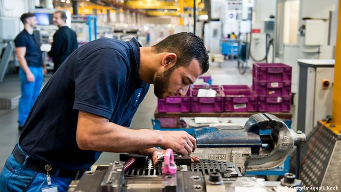 A refugee from Syria who came to Germany in 2014 trains and works at the BMW factory in Munich, Germany.