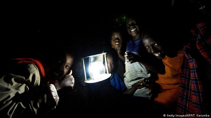 Children with a solar-powered LED lamp in Kenya