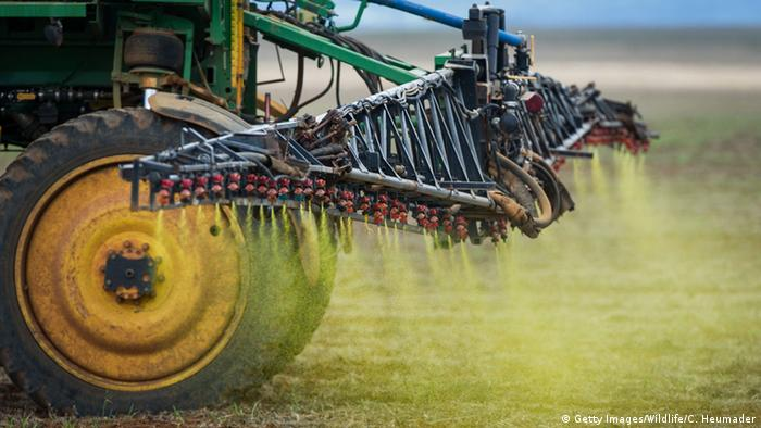 Herbicide is sprayed on a soybean field by a tractor