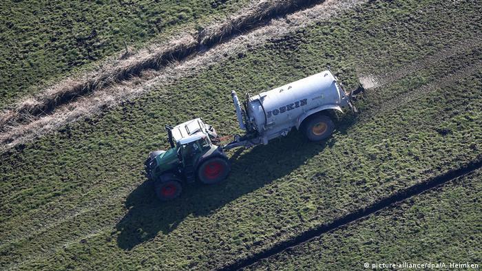 Caminhão dispersa esterco num campo agrícola na Alemanha
