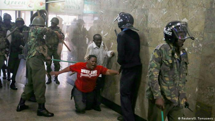 Kenyan police beats up a protester in Nairobi, as the man falls helplessly to the ground