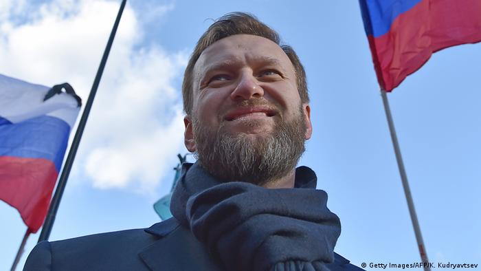 Head shot of Russian Opposition leader Alexei Navalny with two Russian flags waving in the wind behind him.