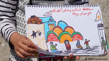A refugee girl holding a painting (photo: Marianna Karakoulaki)