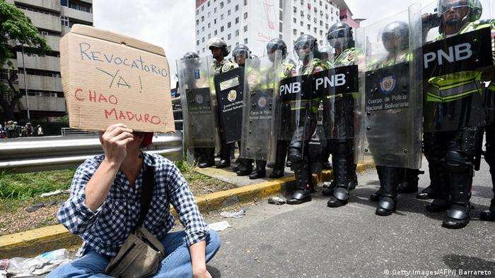 A woman holds a sign that reads: Recall now! Bye Maduro.