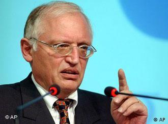 EU Commissoner Günter Verheugen raises a finger while speaking into a microphone