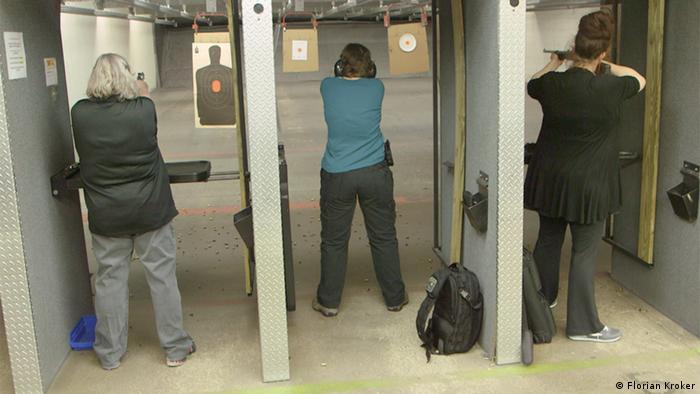 Женщины стреляют по мишеням в тире.