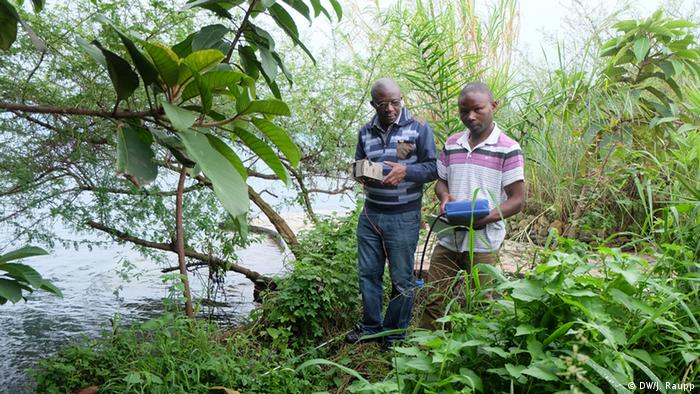 Two men carry instruments to measure carbon dioxide levels in Lake Kivu, DRC.