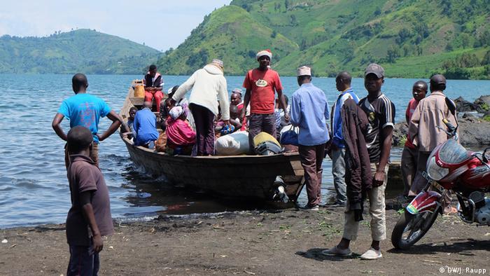 Fishermen inside a wooden canoe as other men look on.