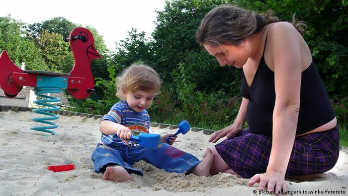 Deutschland Schwangere Mutter mit kleinem Jungen auf dem Spielplatz
