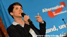 Frauke Petry speaks in front of an AfD logo